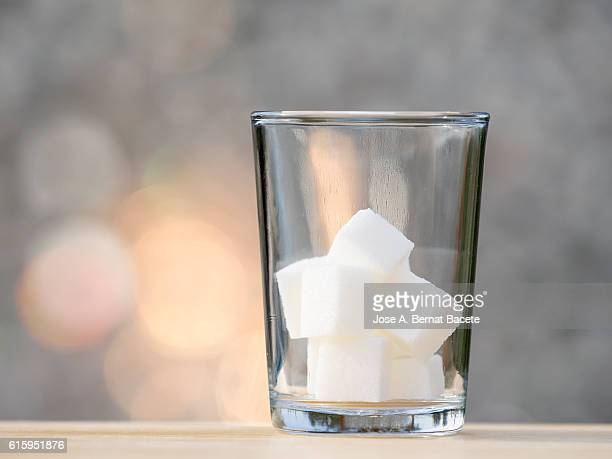 Glass of crystal with nine lumps of sugar cube,  equivalent to a tin of drink of refreshment