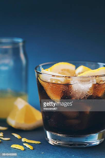 Glass of Cuba Libre in front of blue background