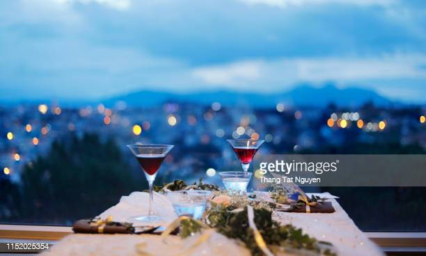 glass of drink by the window with city background at night - romanticism stock pictures, royalty-free photos & images