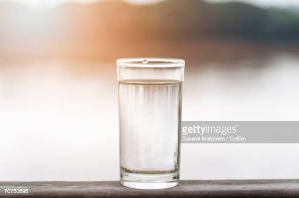 Glass Of Drinking Water On Railing Against River During Sunset