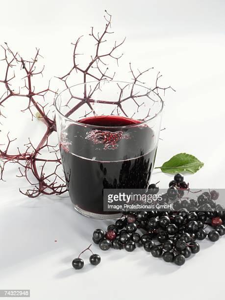 A glass of elderberry & fresh elderberries