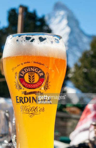 a glass of erdinger beer in front of the matterhorn - mountain logo stock photos and pictures