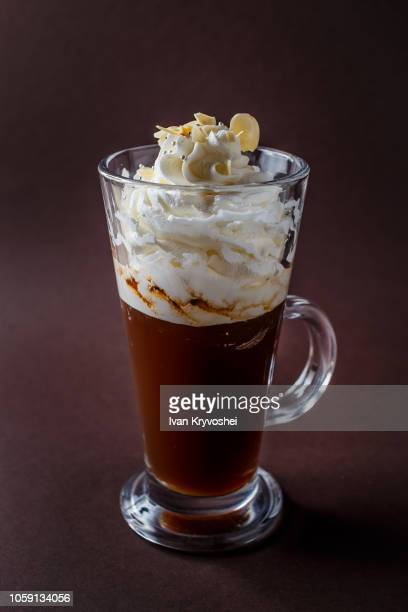 Glass of frappucino with whipped cream and almonds shaving on elegant dark brown background