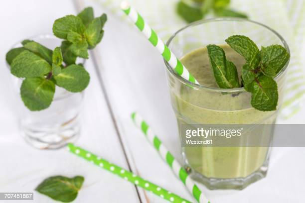 Glass of green smoothie garnished with mint leaves