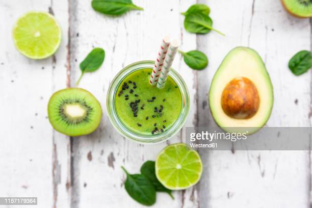 glass of green smoothie with avocado, spinach, kiwi and lime - smoothie stockfoto's en -beelden