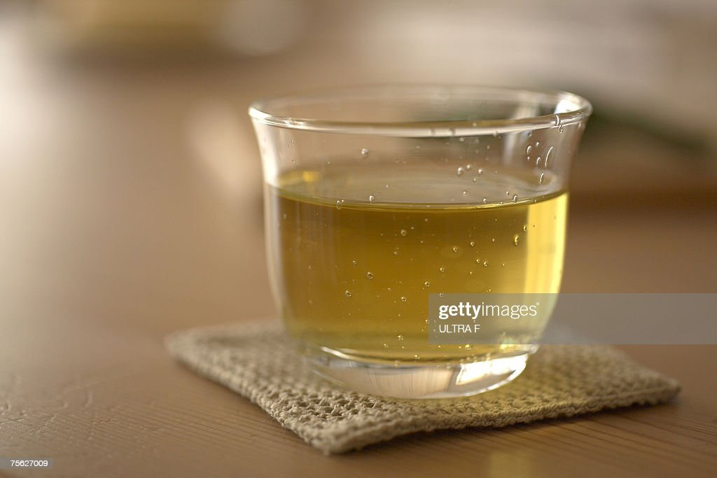 Glass of green tea on coaster, close-up : Foto de stock