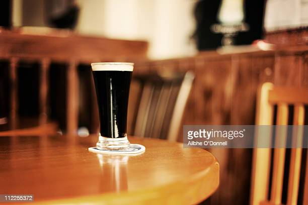 Glass of Guinness on pub table