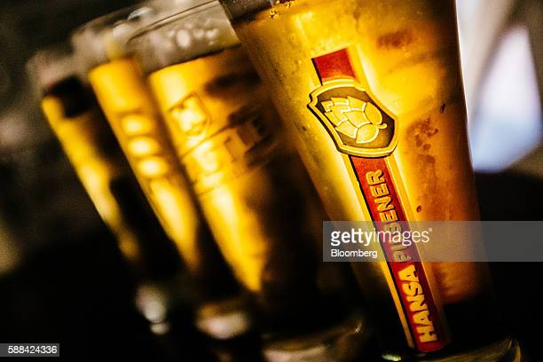 A glass of Hansa Pilsner sits beside Castle brand lagers in the sample room in this arranged photograph at SABMiller Plc's Newlands brewery in Cape...