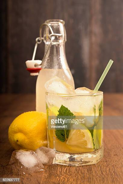 Glass of home made lemonade splash with slices of lemon and clip-top bottle