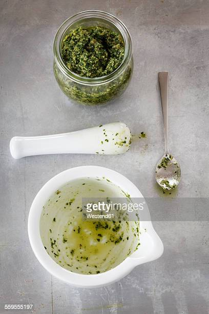 Glass of homemade parsley pesto and empty mortar