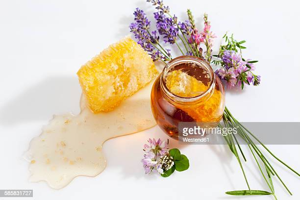 Glass of honey, honeycomb and wild flowers