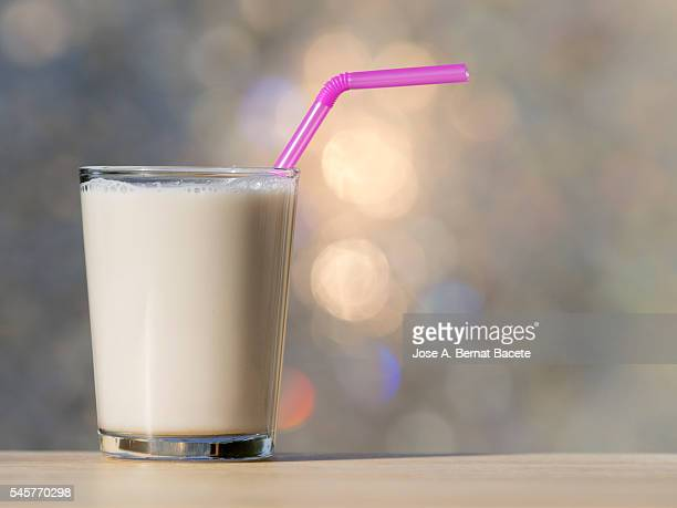 Glass of horchata of chufa, on a table lit by sunlight