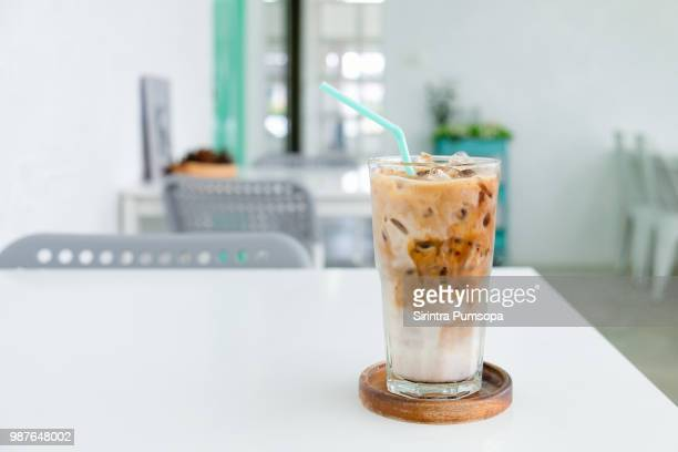 a glass of ice coffee on the white table in coffee shop. - iced coffee stock pictures, royalty-free photos & images