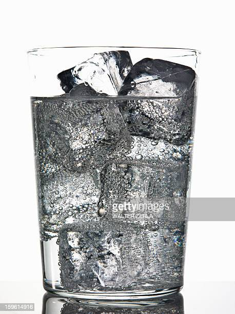 Glass of ice cubes in fizzy drink