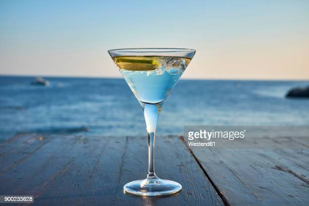 glass of ice-cooled martini with lime slice in front of the sea - martini glass stock pictures, royalty-free photos & images
