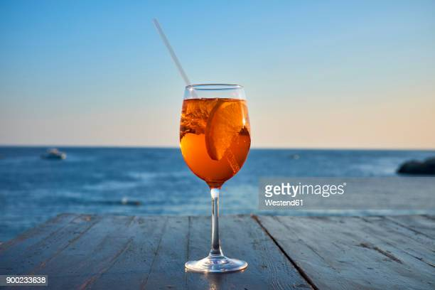 glass of ice-cooled spritz with orange slice in front of the sea - bibita foto e immagini stock