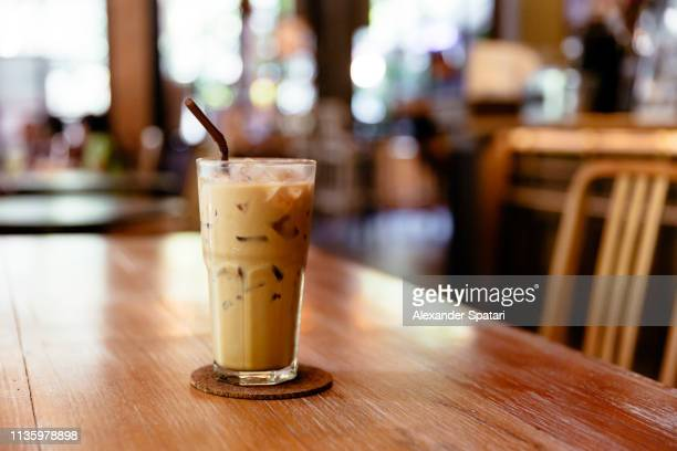 glass of iced coffee on the table in a coffee shop - iced coffee stock pictures, royalty-free photos & images