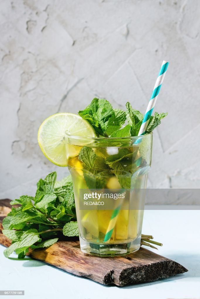 Gl Of Iced Green Tea With Lime Lemon Mint And Ice Cubes On Wooden