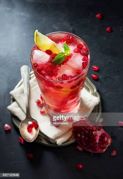 A glass of iced pomegranate juice with lemon slice on dark moody background.