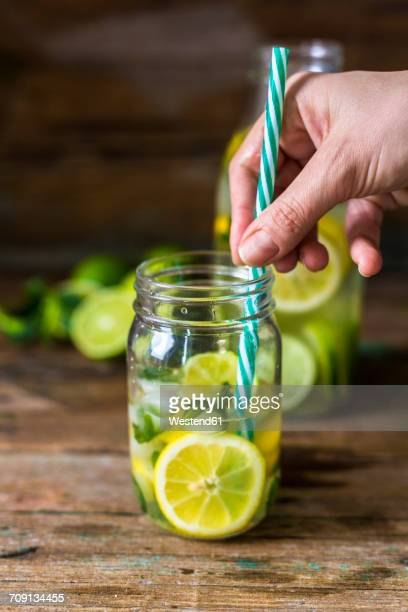 Glass of infused water with lemon, lime, mint leaves and ice cubes