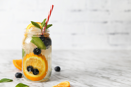 Glass of infused water with orange, blueberries and mint on ice - gettyimageskorea