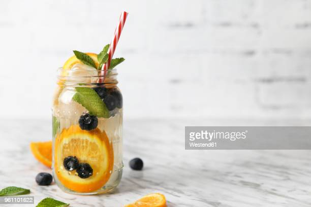 glass of infused water with orange, blueberries and mint on ice - infused water stock pictures, royalty-free photos & images