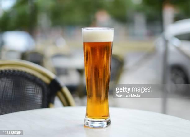 a glass of ipa on an outdoor table - vaso de cerveza fotografías e imágenes de stock