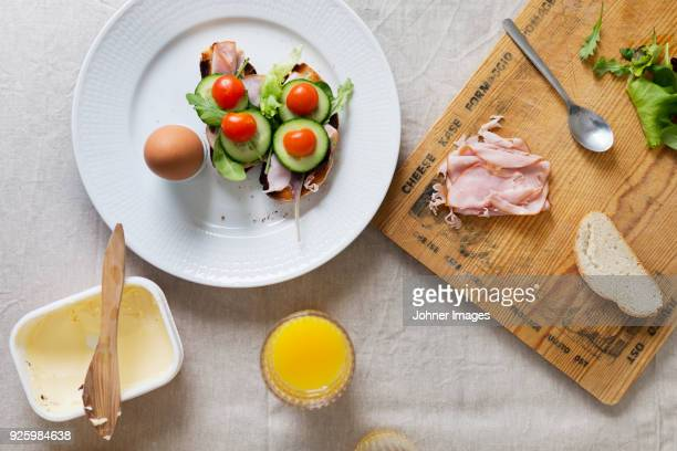 Glass of juice, hard-boiled eggand sandwiches on white plate