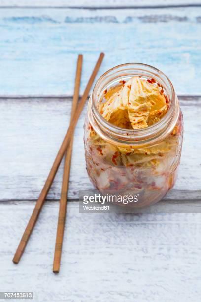 glass of kimchi and chopsticks on wood - キムチ ストックフォトと画像