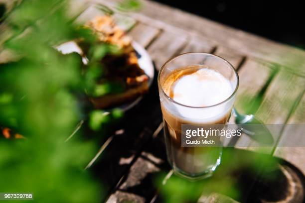 Glass of Latte Macchiato and cake outdoor.