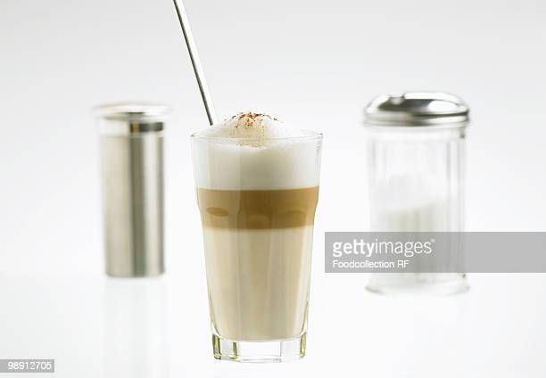 Glass of latte macchiato with sugar and cocoa shakers, close-up