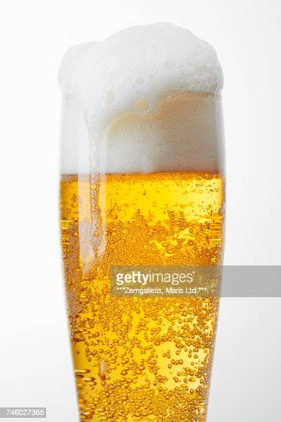 a glass of light beer with overflowing beer foam - carbon dioxide stock photos and pictures