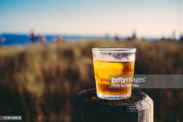 Glass of liqueur on wooden post at the coastline