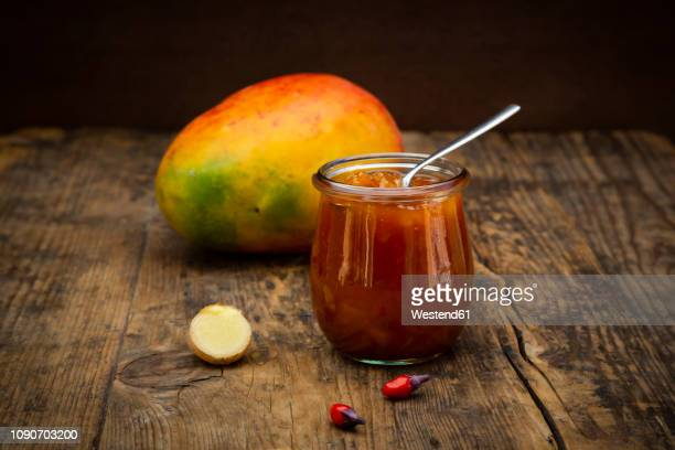 Glass of mango chutney with ginger and chili
