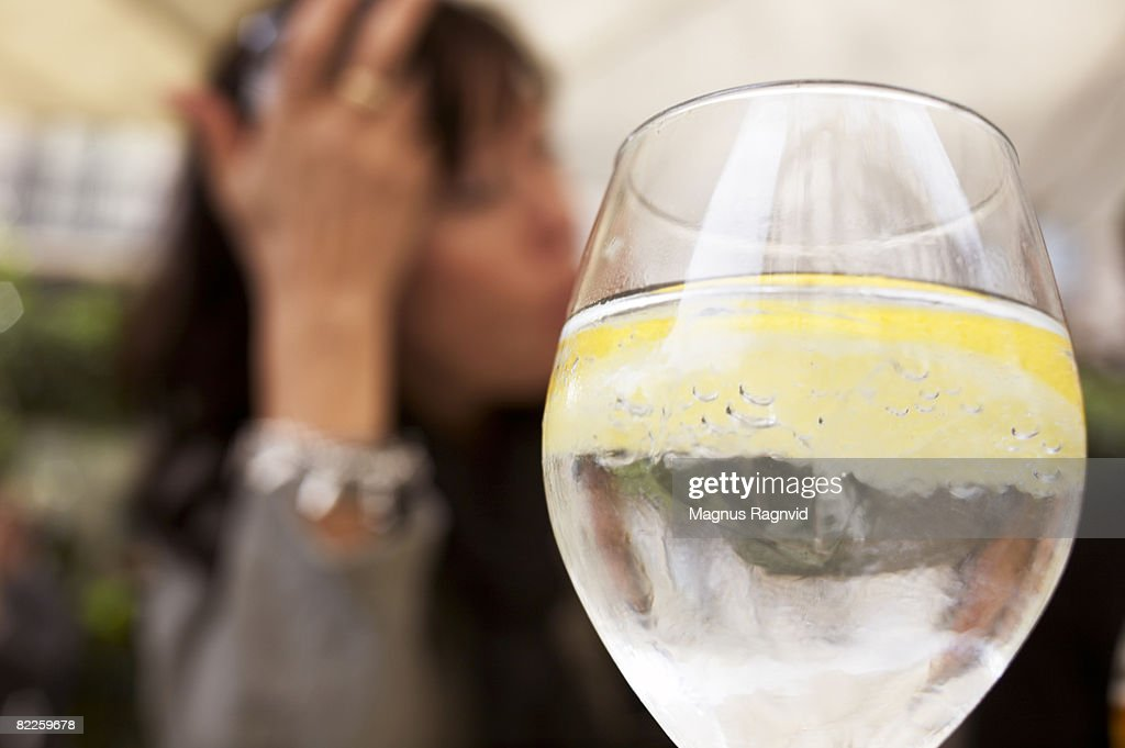 A glass of mineral water and woman in the background. : Stock Photo