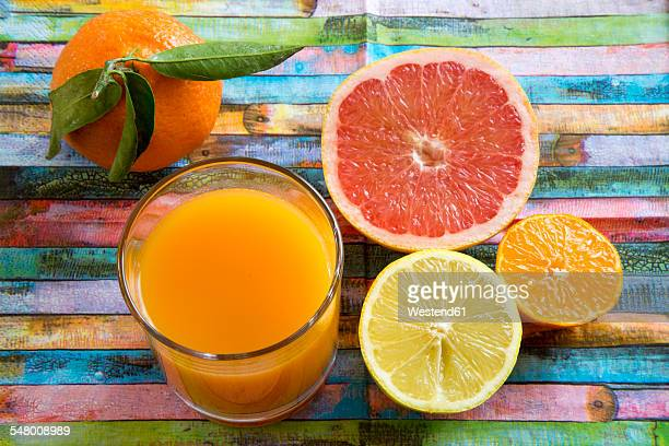 Glass of multivitamine juice and differnet citrus fruits