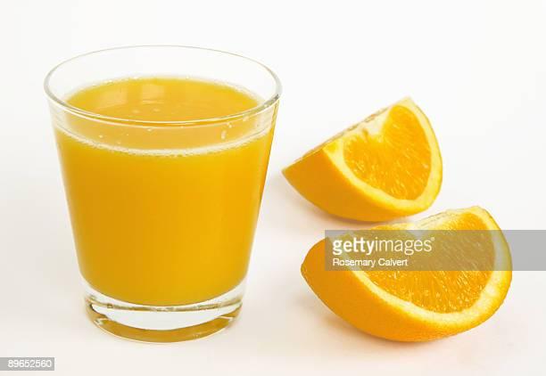 Glass of orange juice and two segments of orange.