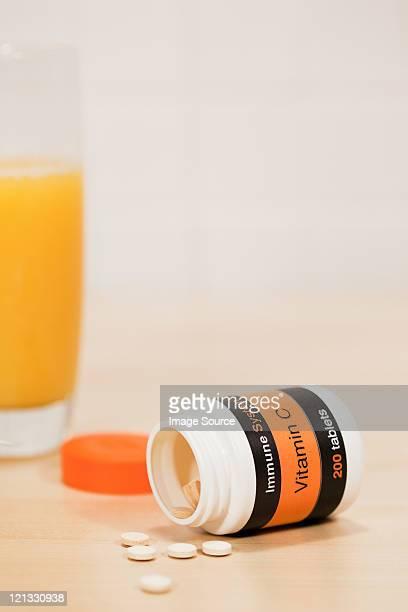 Glass of orange juice and vitamin c tablets