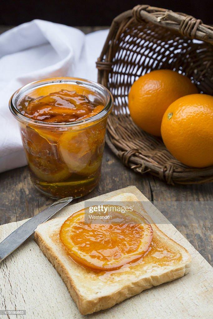Glass of orange marmalade with orange slices and toast : Stock Photo