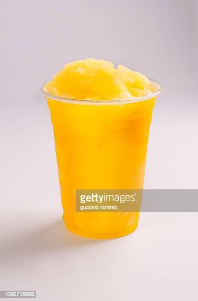 glass of orange slush milkshake smoothie - slush stock photos and pictures