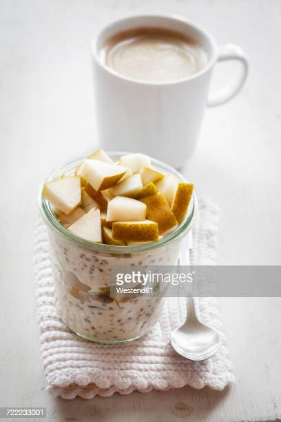 Glass of overnight oats with chia seeds, almond milk and pears