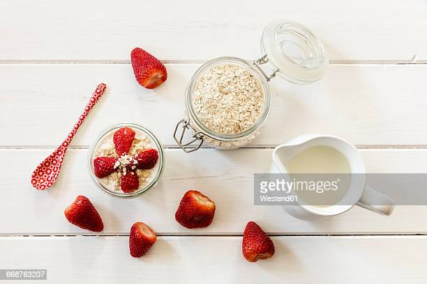 Glass of overnight oats with strawberries and milk jug on wood