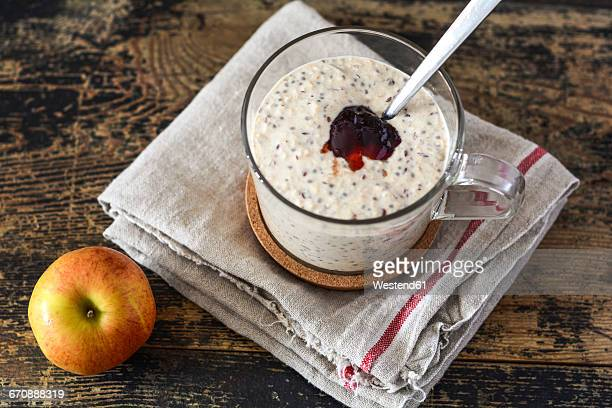 Glass of porridge with jam, linseed and chia seed and an apple on wood