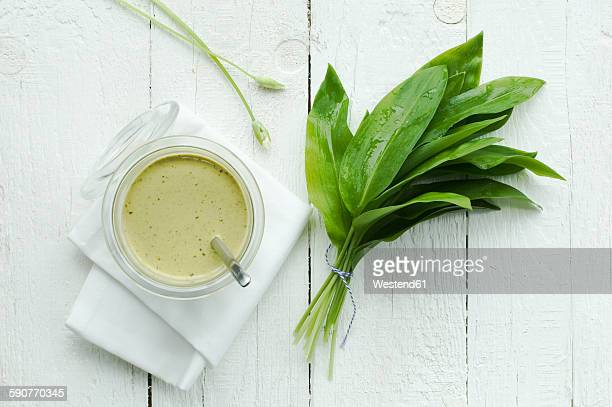 Glass of ramson pesto and bunch of fresh ramson on white wood