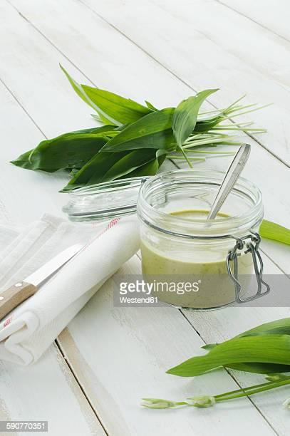 Glass of ramson pesto and fresh ramson on white wood