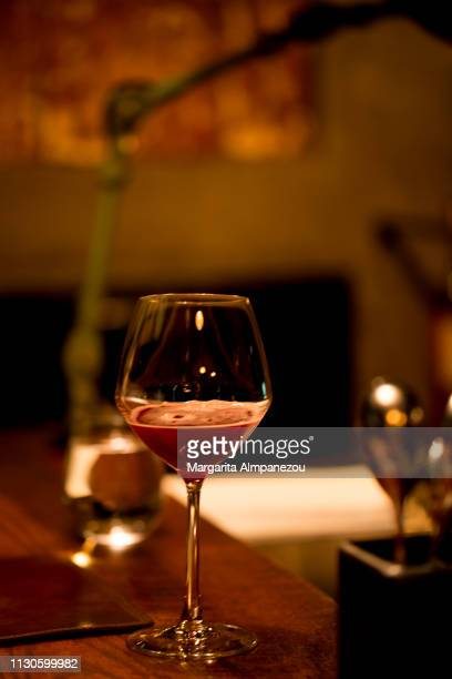 Glass of red sparkling wine on a premium wooden bar surface