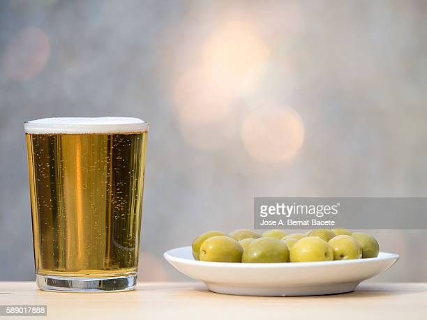 Glass of red wine and bowl of green olives on a wooden table outside, lit by sunlight