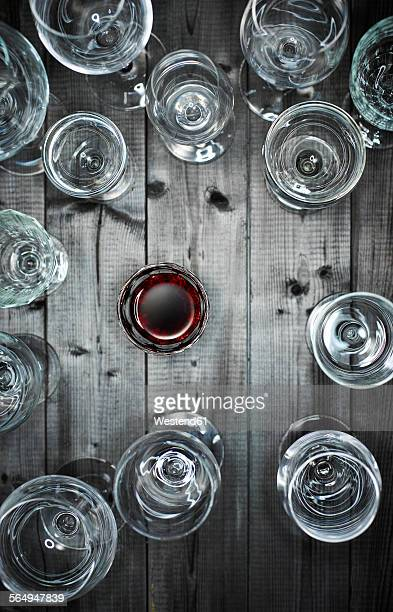 Glass of red wine and empty wine glasses on wood