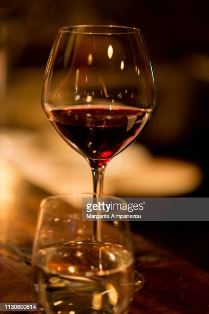 Glass of red wine and water on a premium wooden bar surface