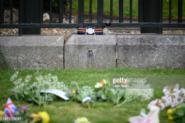 Glass of red wine is seen among the floral tributes to Prince Philip, Duke Of Edinburgh who died at age 99, outside Windsor Castle on April 10, 2021...